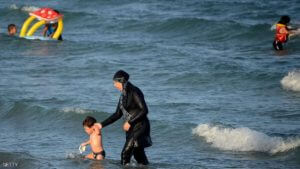 """A Tunisian woman wearing a """"burkini"""", a full-body swimsuit designed for Muslim women, walks in the water with a child on August 16, 2016 at Ghar El Melh beach near Bizerte, north-east of the capital Tunis.  / AFP / FETHI BELAID        (Photo credit should read FETHI BELAID/AFP/Getty Images)"""