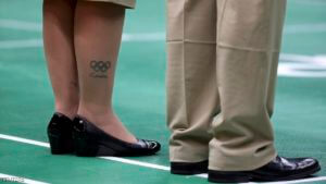 """2016 Rio Olympics - Badminton - Women's Singles Group Play - Riocentro - Pavilion 4 - Rio de Janeiro, Brazil - 14/08/2016. A tattoo of the Olympic rings with the word """"London"""" beneath it is seen on the leg of one of the umpires. REUTERS/Marcelo del Pozo FOR EDITORIAL USE ONLY. NOT FOR SALE FOR MARKETING OR ADVERTISING CAMPAIGNS."""