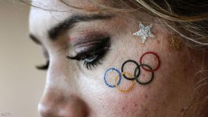 A volunteer wearing a sticker tattoo of the Olympic rings waits for the start of competition at the Lagoa Rodrigo de Freitas in Rio de Janeiro after rowing was delayed during the Rio 2016 Olympic Games on August 7, 2016. / AFP / JEFF PACHOUD        (Photo credit should read JEFF PACHOUD/AFP/Getty Images)